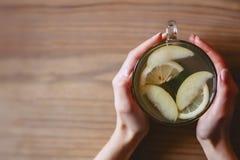 Una taza de té caliente con la menta y el limón en las manos de mujeres fotografía de archivo