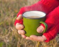 Una taza de té caliente en manos femeninas, al aire libre Imágenes de archivo libres de regalías