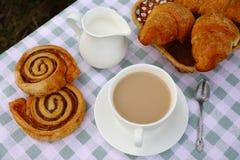 Una taza de té con crema y la panadería imagen de archivo