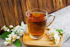 Una taza de té con el jazmín florece en fondo de madera marrón Imagenes de archivo