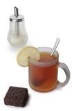Una taza de té con el limón, el azúcar y el chocolate Imagen de archivo libre de regalías
