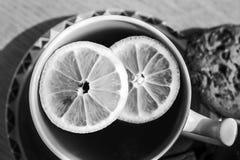 Una taza de té con el limón junta las piezas - de blanco y negro Imagenes de archivo