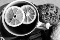 Una taza de té con el limón junta las piezas - de blanco y negro Fotografía de archivo