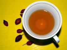 Una taza de té con las caderas y los escaramujos Fotografía de archivo libre de regalías