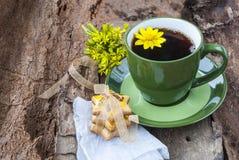 Una taza de té con las galletas en un fondo de madera Fotografía de archivo