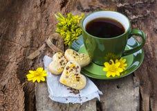 Una taza de té con las galletas en un fondo de madera Foto de archivo libre de regalías