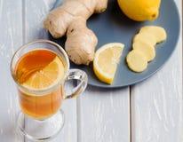 Una taza de té del jengibre con el limón en un fondo de madera Foto de archivo