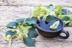 Una taza de té del tilo cerca de las flores de la cal en el fondo de viejos tableros flores del tilo y una taza de té imagen de archivo libre de regalías