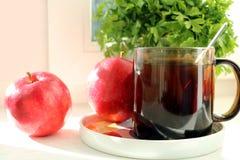 Una taza de té delicioso frío negro fragante en un platillo en los rayos del sol en el alféizar, en la tabla y al lado de los fre Foto de archivo