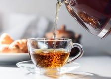Una taza de té en la cual para verter té de la caldera Imágenes de archivo libres de regalías