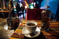 Una taza de té en la tabla al lado de la cachimba Café atmosférico de la calle foto de archivo libre de regalías