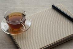 Una taza de té está en el cuaderno y la pluma fotos de archivo libres de regalías