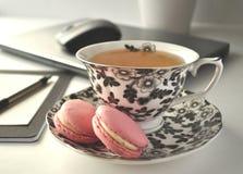 Una taza de té floral blanco y negro con los macarrones franceses rosados en una tabla con el ordenador portátil y un ratón - un  fotos de archivo libres de regalías