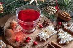 Una taza de té de la cadera color de rosa con las galletas del pan de jengibre de la Navidad fotos de archivo libres de regalías