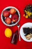 Una taza de té, limón en un fondo rojo, comida y bebida, cuchillo y bifurcación, tiempo del té, opinión de tiempo de desayuno des Fotos de archivo