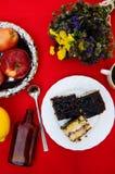 Una taza de té, limón en un fondo rojo, comida y bebida, cuchillo y bifurcación, tiempo del té, opinión de tiempo de desayuno des Fotografía de archivo
