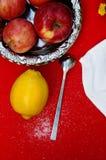 Una taza de té, limón en un fondo rojo, comida y bebida, cuchillo y bifurcación, tiempo del té, opinión de tiempo de desayuno des Imágenes de archivo libres de regalías