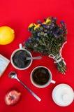 Una taza de té, limón en un fondo rojo, comida y bebida, cuchillo y bifurcación, tiempo del té, opinión de tiempo de desayuno des Foto de archivo