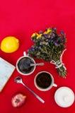 Una taza de té, limón en un fondo rojo, comida y bebida, cuchillo y bifurcación, tiempo del té, opinión de tiempo de desayuno des Fotografía de archivo libre de regalías