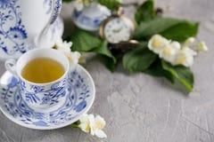 Una taza de té magnífica con té verde y el jazmín florece Imagen de archivo
