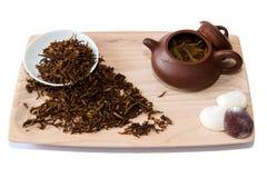 Una taza de té negro con la tetera en el fondo blanco Imagen de archivo libre de regalías