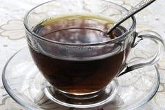 Una taza de té negro está en la tabla fotografía de archivo libre de regalías