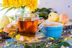 Una taza de té negro y de atasco de las peras en un cuenco Imagenes de archivo
