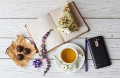Una taza de té, un cuaderno, varios caramelos, un collar nad florece fotos de archivo