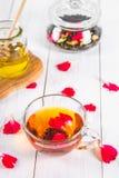 Una taza de té, una poder de miel y un tarro con un té floral herbario negro en una tabla de madera blanca Visión superior Imagenes de archivo