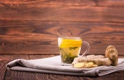 Una taza de té Una taza en un fondo de madera Una taza hermosa con el limón cortado y la raíz orgánica del jengibre Copie el espa Foto de archivo