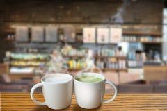 Una taza de té verde caliente y una taza de café caliente en la cafetería fotos de archivo libres de regalías