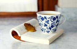 Una taza de té verde en una tabla de mármol con un libro abierto y una a Imágenes de archivo libres de regalías