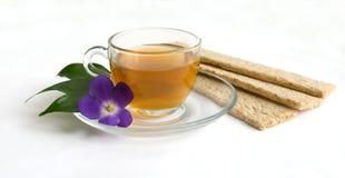 Una taza de té verde y de pequeños panes Imagen de archivo