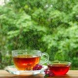 Una taza de té y de miel de la flor por la ventana Está lloviendo fuera de la ventana Vidrio en las gotas de la lluvia Fotografía de archivo