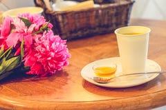 Una taza de té y de peonías, miel, cuchara descansa sobre el platillo, tabla de madera, casa acogedora fotografía de archivo
