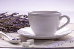 Una taza de té y flores de la lavanda en la materia textil Imagenes de archivo