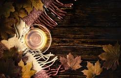 Una taza de té y de hojas de arce en viejos tableros con la pintura descolorada, y tela escocesa a cuadros Imagenes de archivo