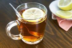 Una taza de té y de limón en la tabla Imagen de archivo libre de regalías