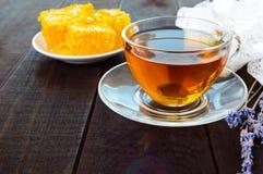 Una taza de té y panal en una tabla de madera oscura Fotos de archivo