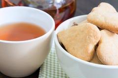 Una taza de té y un cuenco con las galletas para el desayuno Fotos de archivo