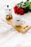Una taza del café, café en los tableros de madera, un ramo de rosas rojas en un fondo blanco Fotos de archivo libres de regalías