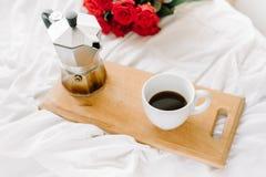 Una taza del café, café en los tableros de madera, un ramo de rosas rojas en un fondo blanco Foto de archivo