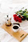 Una taza del café, café en los tableros de madera, un ramo de rosas rojas en un fondo blanco Imagenes de archivo