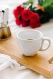 Una taza del café, café en los tableros de madera, un ramo de rosas rojas en un fondo blanco Imágenes de archivo libres de regalías