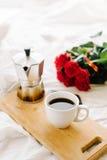 Una taza del café, café en los tableros de madera, un ramo de rosas rojas en un fondo blanco Fotos de archivo