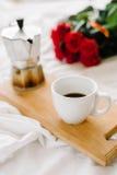 Una taza del café, café en los tableros de madera, un ramo de rosas rojas en un fondo blanco Imagen de archivo