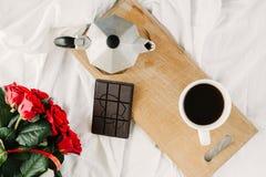 Una taza del café, café en los tableros de madera, un ramo de rosas rojas en un fondo blanco Imagen de archivo libre de regalías