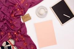 Una taza del café, de un pequeño tablero de madera negro y de una tiza blanca, papel rosado con metas de los Años Nuevos Bufanda  Fotografía de archivo libre de regalías