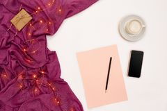 Una taza del café, papel elegante, rosado negro con metas de los Años Nuevos Luces de la bufanda y de la Navidad en el fondo blan Imagen de archivo libre de regalías