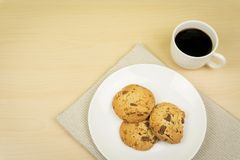 Una taza del café, tres pedazos de galletas de microprocesador de chocolate en un plato redondo blanco Fotos de archivo libres de regalías
